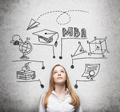 A young lady is thinking about MBA degree. Educational chart is drawn behind her. A concept of further business education. Concrete background Royalty Free Stock Image