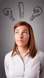 Young lady thinking with question marks overhead Royalty Free Stock Images