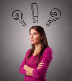 Young lady thinking with question marks overhead Stock Image
