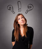 Young lady thinking with question marks overhead Royalty Free Stock Photography