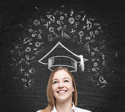 Young  lady is thinking about studying at the university. Educational icons are drawn on the black chalk board. Stock Photo