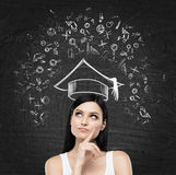 Young lady is thinking about studying at the university. Educational icons are drawn on the black chalk board. Royalty Free Stock Photos