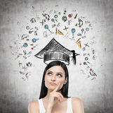 Young lady is thinking about studying at the university. Educational icons are drawn on concrete wall. Stock Photo
