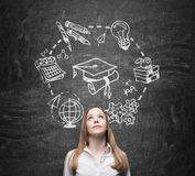 Young  lady thinks about studying and graduation. Educational icons are drawn on the black chalkboard. Stock Photo