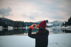 Young lady tourist admire all the beauty of nature with a big blue lake and snowy forest and mountain, she is very happy