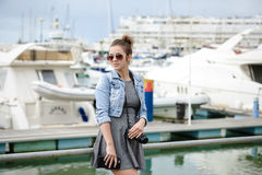 Young lady tourist holding camera standing in harbour shooting yachts Stock Photo