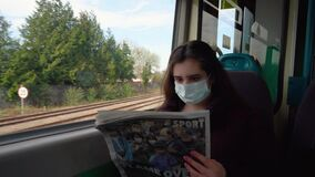 A young lady travels by train in a medical mask and reads a newspaper