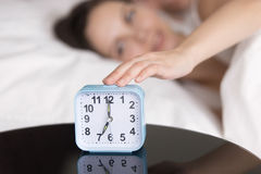 Young lady turning off ringing alarm clock in the morning Royalty Free Stock Photo