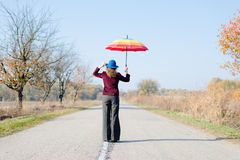 Young lady under rainbow colored parasol standing Stock Photos