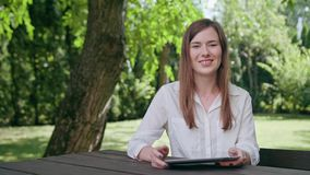 Young lady using an ipad in the park. A young attractive lady sitting on the bench at the table in the park and using an ipad. Medium shot. Soft Focus stock footage