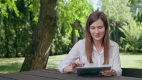 Young Lady Using an iPad in the Park. A young attractive lady sitting on the bench at the table in the park and using an ipad. Medium shot. Soft Focus Royalty Free Stock Photography