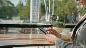 A Young Lady Using a Smartphone in the Cafe. Close-up shot. Soft focus stock video
