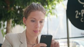 A Young Lady Using a Smartphone in the Cafe. A young beautiful lady using a smartphone in the cafe. Close-up shot. Soft focus stock video footage