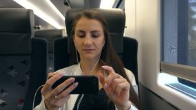 A Young Lady Using a Smartphone in the Train. Medium shot stock footage