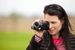 Young lady using video camera outdoors. Portrait of a young brunette woman using a camcorder outdoors Stock Photo