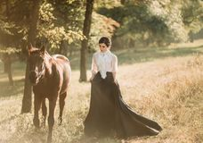 A young lady in a vintage dress with a long train, walks with a horse through the forest glades. An ancient, collected hairstyle, royalty free stock photography