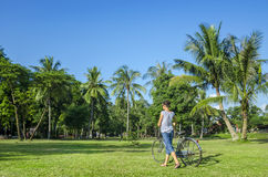 Young lady walking, classic bike and palm trees Royalty Free Stock Photo