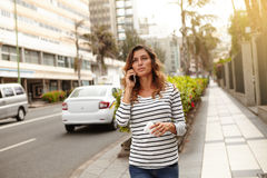 Young lady walking with confidence on city street. Young lady of caucasian ethnicity walking with confidence on city street and talking on cell phone royalty free stock photos
