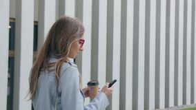 A Young Lady Walking and Using a Smartphone stock image