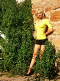 Young lady on the wall. An blond young pretty lady standing on an old stone wall in an yellow Royalty Free Stock Image