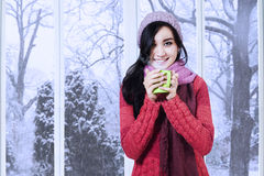 Young lady wearing sweater enjoy warm drink Stock Images