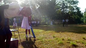 Young lady in white dress silhouette holds blue cricket bat. Colombo/SRI LANKA - APRIL 05 2019: Young lady in white dress silhouette holds blue cricket bat with stock video footage