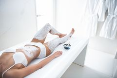 Young lady in white lingerie having therapeutic procedure with white clay. Healing skincare. Female well shaped body with white cosmetic mask on legs and belly royalty free stock photos