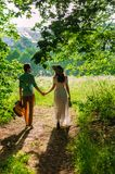 Young lady in a white summer dress with a flower. Young lady in white summer dress with flower wreath on her head walks in the woods with a young man stock image