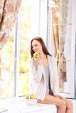 Young lady on the windowsill with seasonal fruits Stock Image
