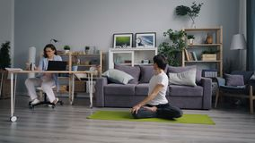 Young lady working with computer while boyfriend doing sports yoga in house. Young lady is working with computer while sporty boyfriend is doing sports yoga in stock video footage