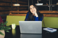Young lady working at laptop in modern office hub. Stock Photos