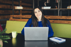 Young lady working at laptop in modern office hub. Royalty Free Stock Image