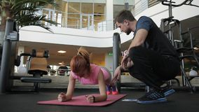 The young lagy is doing plank and her male couch is helping her in the gym. The sprtswoman is standing on the elbows and the man in black sportswear sits near stock footage
