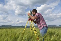 Young land surveyor in a wheat field. Selective focus royalty free stock photo