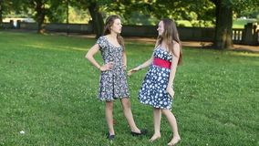 Young lasses talking among themselves outdoors. Teenage girls gossiping. Young cute lasses talking among themselves outdoors. Teenage girls gossiping stock video
