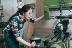 Young lathe company woman worker wearing goggles. Beautiful young lathe company woman worker wearing goggles adjusting milling machining doing parts components stock images