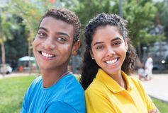 Young latin american couple with colorful shirts back to back Royalty Free Stock Image