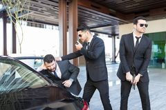 Hispanic Boss Getting In Car With Help Of Bodyguards stock photography