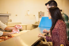 Young Latin couple buying meat Royalty Free Stock Photography