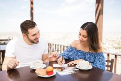 Cheerful young woman writing postcards. Young latin couple writing memories behind hard copy of images about trip during breakfast at terrace caf stock image