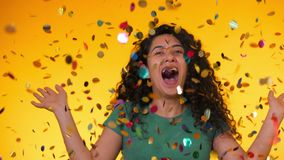 Young latin girl with curly hair dancing and having fun in confetti rain on yellow background. Woman celebrating stock footage