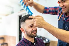 Young Man Getting a Hairstyle in a Barbershop royalty free stock images