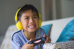Young Latin little child excited and happy playing video game online with headphones holding controller having fun sitting on couc stock photos