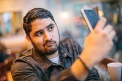 Beautiful latin man posing takes selfie on phone. Fun online dating communication. cheating cool face Royalty Free Stock Image