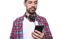 Young latin man typing on his smartphone. Royalty Free Stock Photos