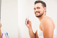 Young Latin man using a nose hair trimmer Royalty Free Stock Photos