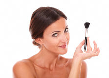 Young latin woman with brush for smooth her face Stock Photo