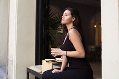 Young latin woman enjoying rest after work day while sitting in sidewalk cafe. Beautiful female tourist holding cup of drink while relaxing in coffee shop after Royalty Free Stock Photography