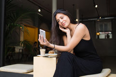 Young latin woman making self portrait on her smartphone digital camera while sitting in sidewalk cafe during lunch break Stock Photos