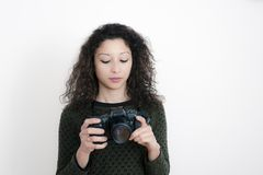 Young latin woman with a camera. Young latin woman with a reflex camera with white background Royalty Free Stock Image